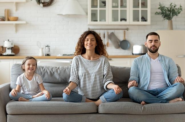 família meditando no sofá
