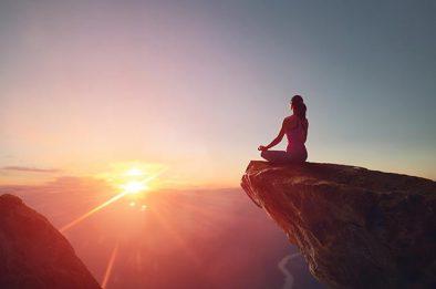 mulher meditando ao pôr-do-sol